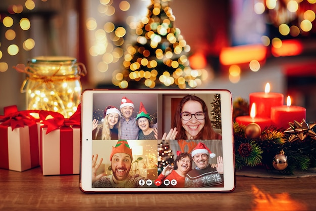 Tablet em uma sala aconchegante com videochamada de natal com a família. conceito de famílias em quarentena durante o natal por causa do coronavírus Foto Premium