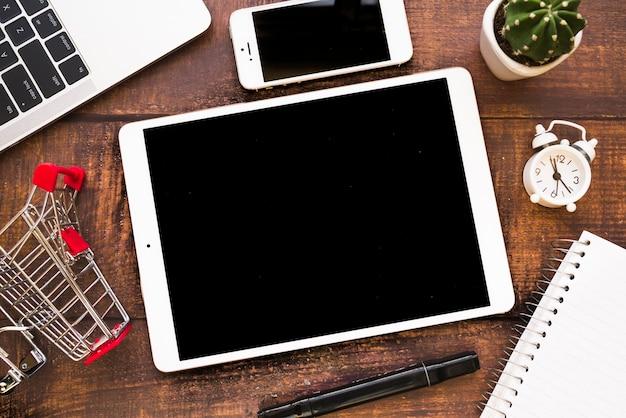 Tablet perto de smartphone, laptop e carrinho de compras Foto gratuita