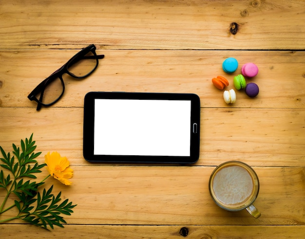 Tablet preto com café quente e doce colorido na mesa de madeira em tom morno Foto Premium