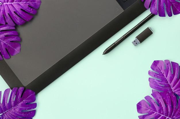 Tablete gráfico e caneta, cartão de memória e folhas de monstera Foto Premium
