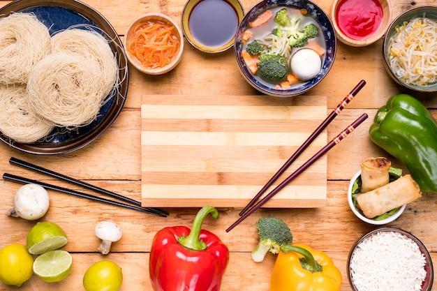 Tábua de cortar com pauzinhos espalhados com comida tailandesa tradicional Foto gratuita