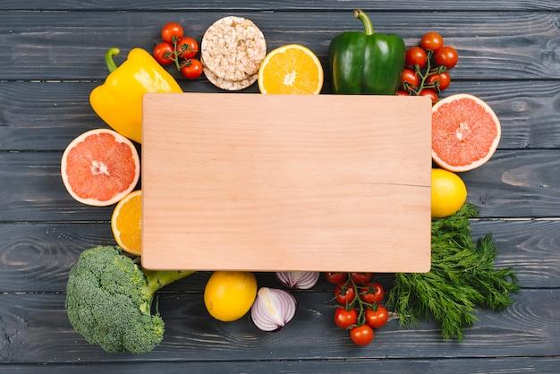 Tábua de cortar de madeira sob os legumes coloridos na mesa de madeira preta Foto gratuita