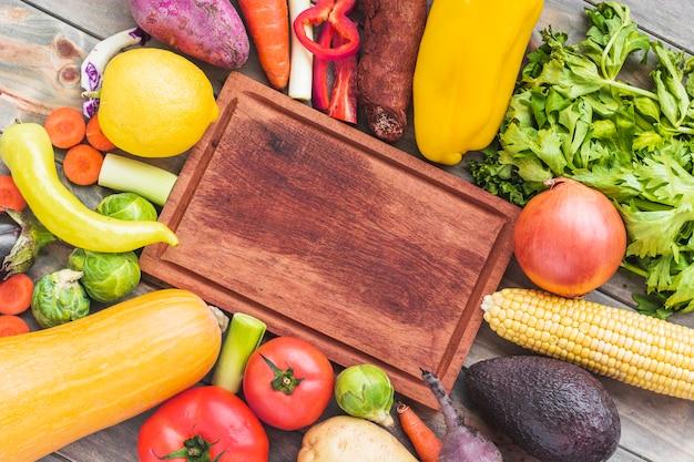 Tábua de madeira rodeada por vários alimentos crus Foto gratuita
