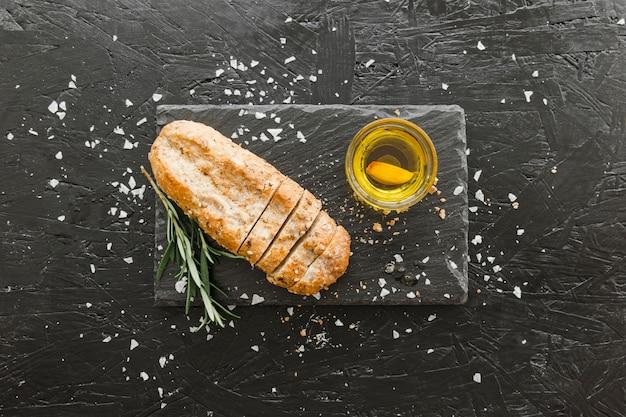 Tábua de pedra com pão e azeite Foto gratuita