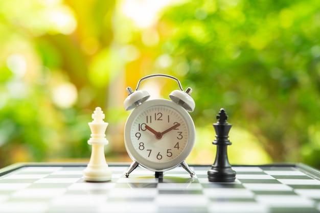 Tabuleiro de xadrez com uma peça de xadrez nas costas negociar nos negócios Foto Premium