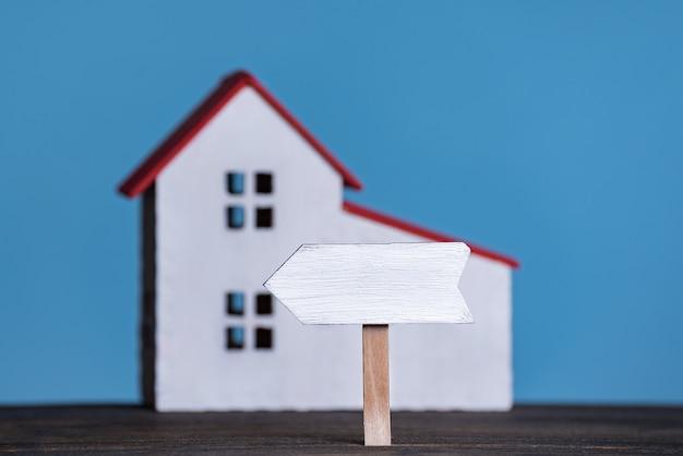 Tabuleta de madeira no fundo da casa. conceito de acomodação própria. fundo azul, vista frontal Foto Premium