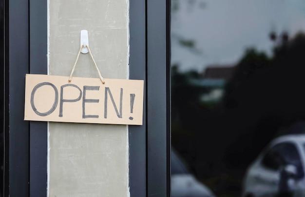 Tabuleta de papel duro marrom closeup com massagem aberta na frente do fundo da loja de café Foto Premium