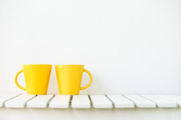 Taça de café amarela na mesa Foto gratuita