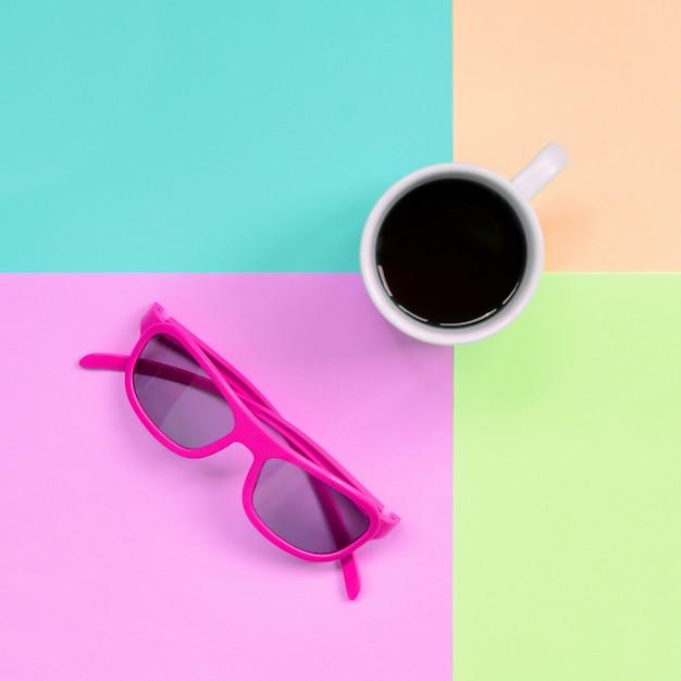 Taça de café branco pequeno e óculos de sol rosa na moda pastel rosa, azul, coral e cores de limão Foto Premium