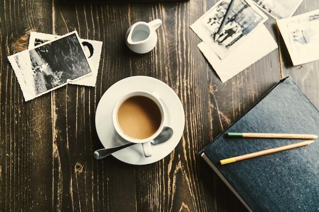 Taça de café em mesa de madeira entre todas as fotos Foto gratuita