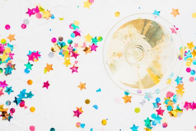 Taça de champanhe com lantejoulas estrela na mesa branca Foto gratuita