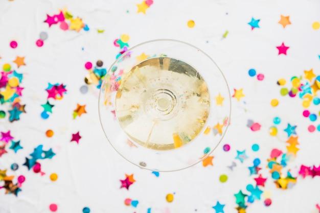 Taça de champanhe com lantejoulas estrela na mesa Foto gratuita