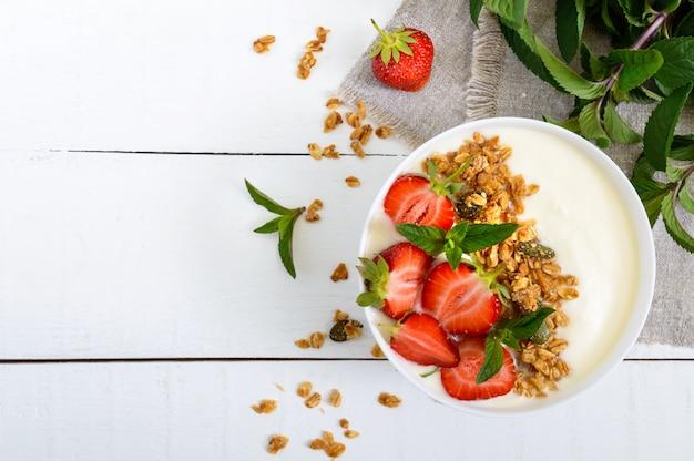 Taça de iogurte, granola e morangos Foto Premium