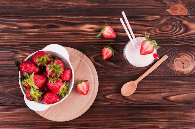 Taça de morangos e batido na mesa Foto gratuita