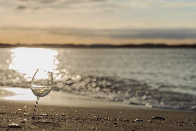 Taça de vinho branco na praia ao pôr do sol Foto Premium