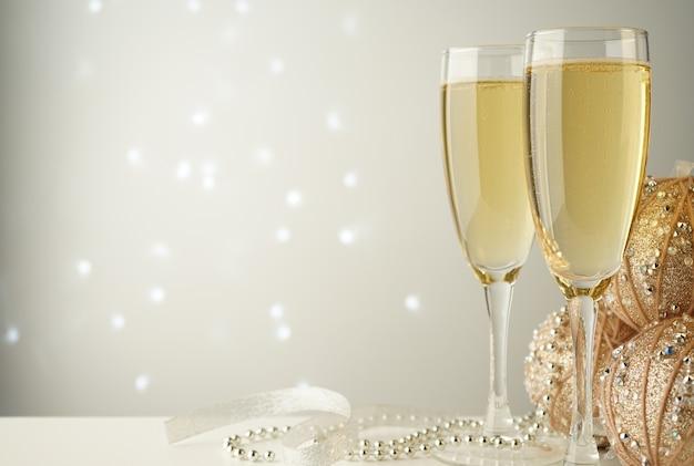 Taças de champanhe perto de bolas de natal e fitas branco-prateadas Foto Premium