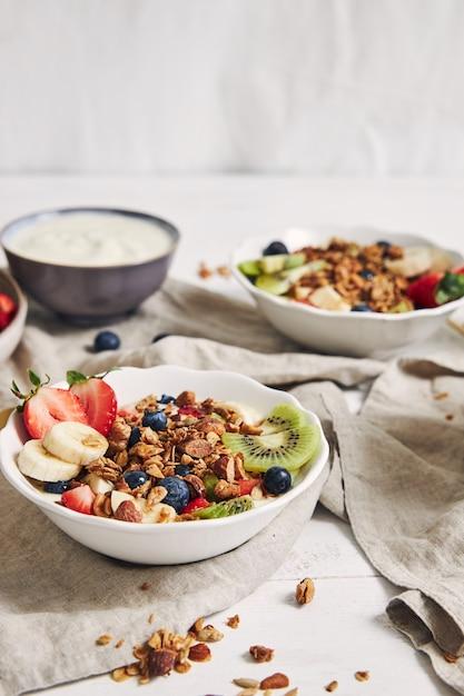 Taças de granola com iogurte, frutas e morangos em uma superfície branca Foto gratuita