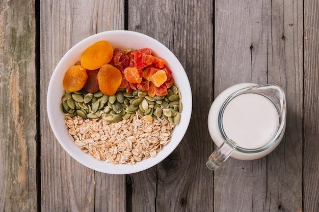 Taças de muesli, sementes de abóbora e frutas secas na tigela com jarro de leite na mesa de madeira rústica Foto gratuita