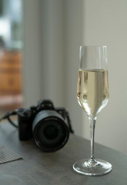Taças de vinho prosecco e câmera na mesa Foto Premium