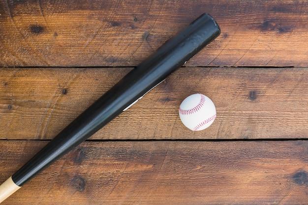 Taco de beisebol e beisebol na mesa de madeira Foto gratuita
