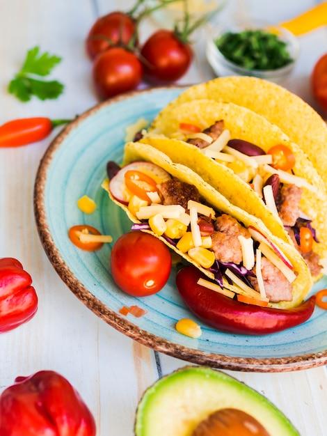 Tacos colocados na mesa perto de legumes Foto gratuita
