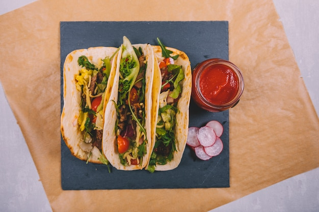 Tacos de carne mexicana com legumes e molho de tomate na ardósia preta Foto gratuita