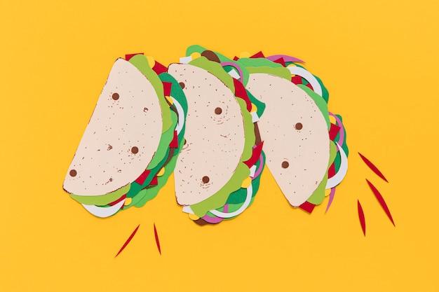 Tacos de papel na vista superior do fundo amarelo Foto gratuita