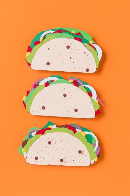 Tacos de papel planos em fundo laranja Foto gratuita