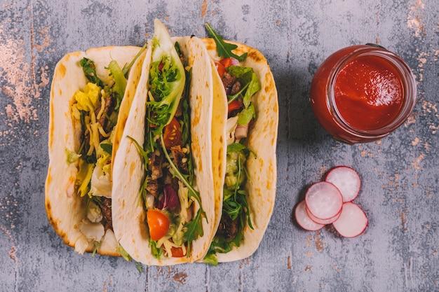 Tacos e vegetais mexicanos da carne na tortilha com molho de tomate no fundo resistido Foto gratuita