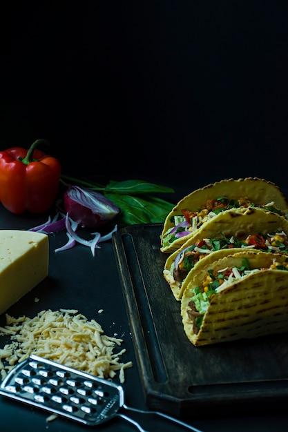 Tacos mexicanos com carne de porco, queijo, milho, cebola e ervas em uma placa de madeira Foto Premium