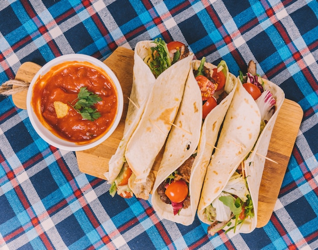 Tacos mexicanos tradicionais; molho de salsa com carne e legumes na tábua de cortar Foto gratuita