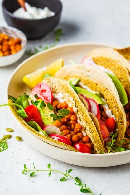 Tacos vegan com grão cozido, abacate, molho e legumes. Foto Premium