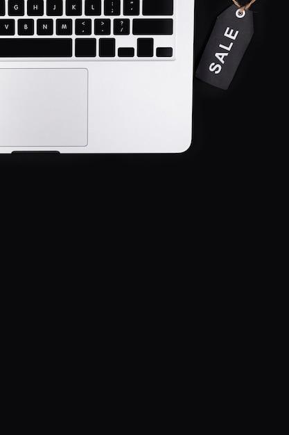Tag de venda preto vista superior perto de laptop Foto gratuita