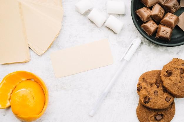Tag em branco com pedaços de chocolate; marshmallow; caneta; biscoitos e casca de laranja Foto gratuita