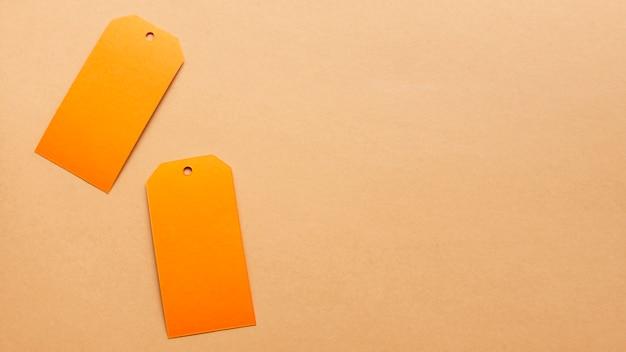 Tags laranja na folha neutra de papelão com espaço de cópia Foto gratuita