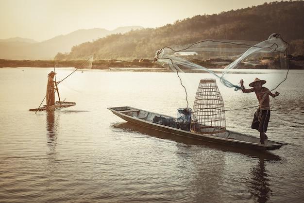 Tailandês pescador no barco de madeira, lançando uma rede para a captura de peixes de água doce no rio natureza Foto Premium