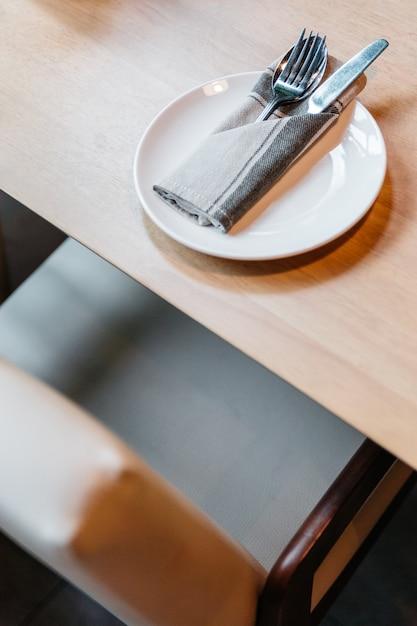 Talheres conjunto incluindo colher, garfo, faca e guardanapo na chapa branca na mesa de madeira. Foto Premium