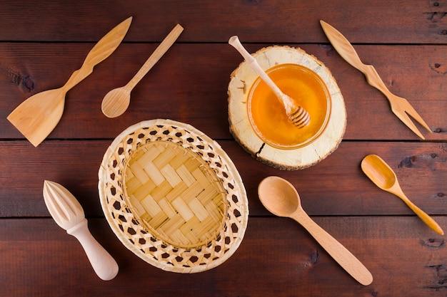 Talheres de madeira, vista superior. talheres e mel em tábuas de madeira. Foto Premium