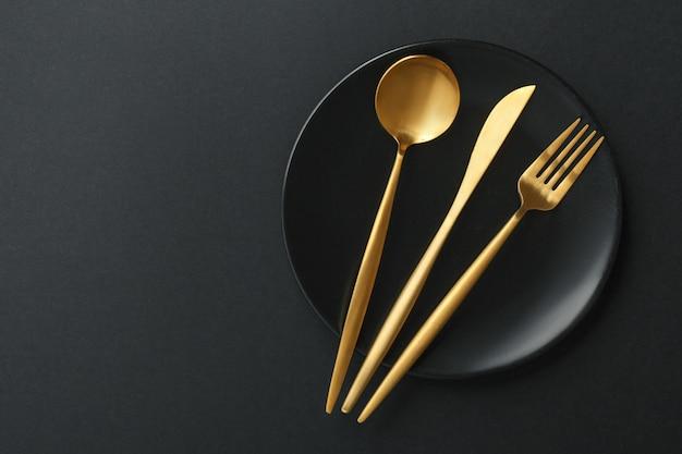 Talheres de ouro em fundo preto Foto gratuita