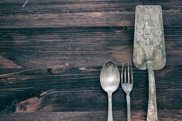 Talheres vintage em fundo de madeira rústica. Foto Premium