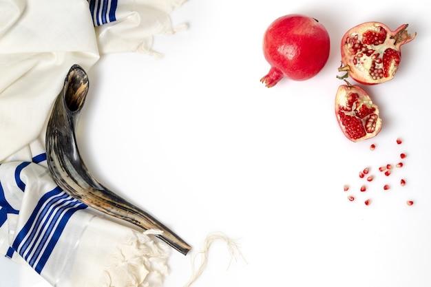 Talit, shofar, romã e sementes de romã, no fundo branco, vista superior Foto Premium