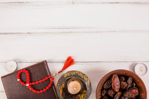 Tâmaras suculentas frescas da palma na bacia com grânulos de oração; velas acesas na mesa de madeira branca Foto gratuita