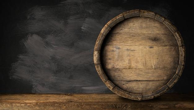 Tambor de cerveja de madeira velho no fundo escuro. Foto Premium