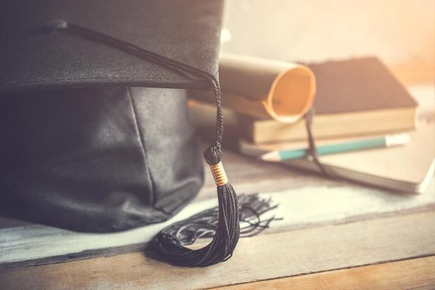 Tampão da graduação, chapéu com papel do grau no conceito de madeira da graduação da tabela. Foto Premium