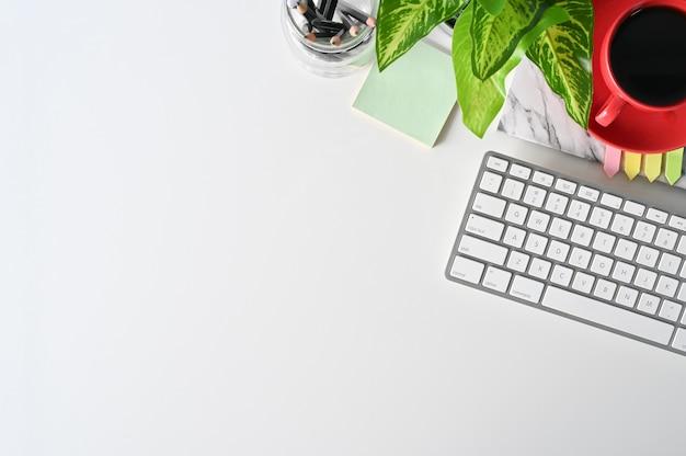 Tampo da mesa da mesa de escritório com a decoração do computador, do auscultadores, do lápis, do café e da planta. Foto Premium