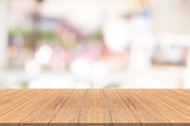 Tampo da mesa de madeira no fundo desfocado do shopping center, espaço para montagem de seus produtos Foto Premium