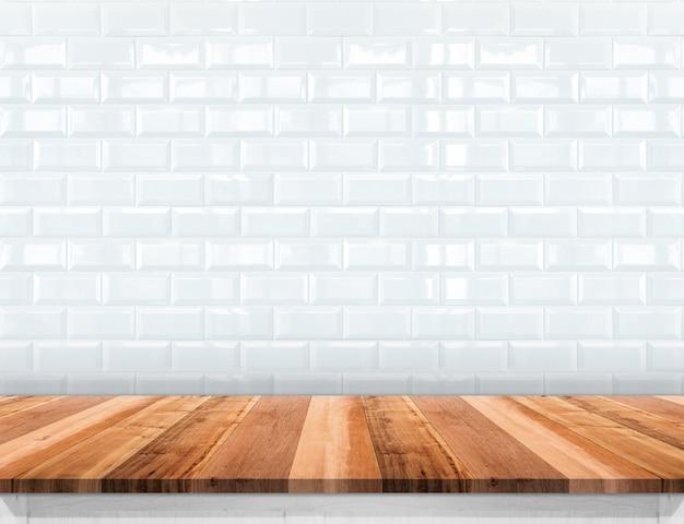 Tampo da mesa de madeira vazio com fundo da parede de azulejo branco cerâmico brilhante Foto Premium