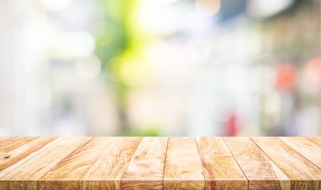Tampo da mesa de madeira vazio na visão borrada do vidro da janela abstrata. para exibição de produtos de montagem ou layout visual chave de design Foto Premium