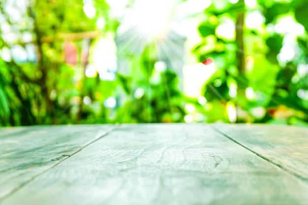 Tampo da mesa de madeira velho vazio com fundo do verde do borrão no tempo do jardim e de manhã. Foto Premium