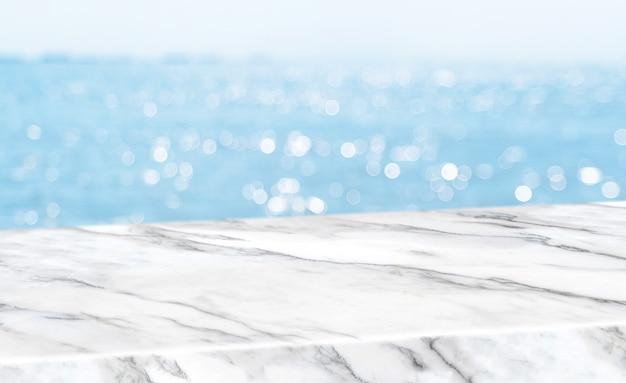 Tampo da mesa de mármore branco brilhante vazio com fundo de boekh de céu e mar de borrão Foto Premium